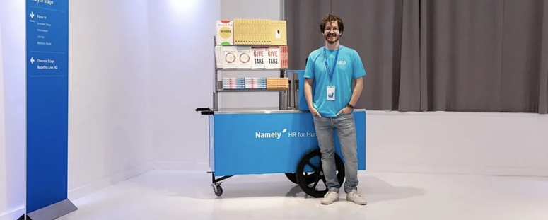 A Namely volunteer stands by the NamelyReads book cart at HRRedefined