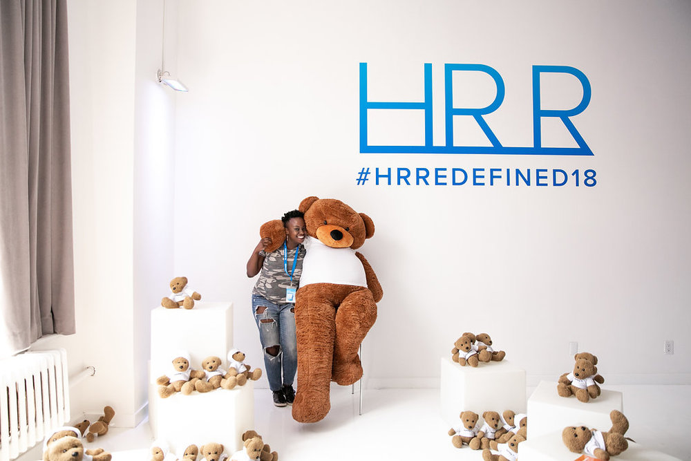 An HR Redefined Attendee poses with the Namely Bear