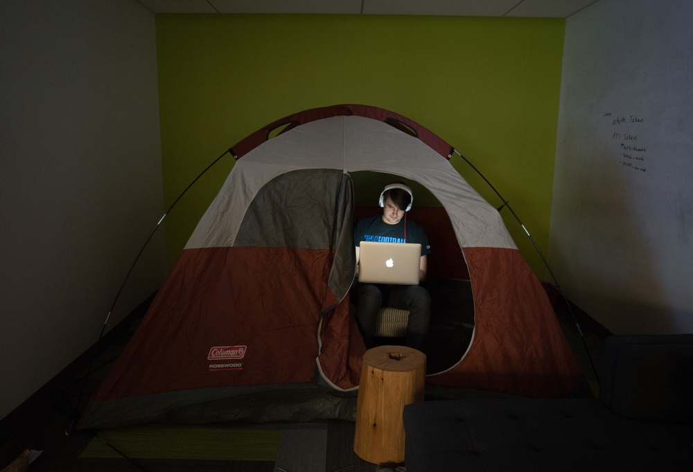 Bobby Tables, Software Developer, hacks away inside a tent.
