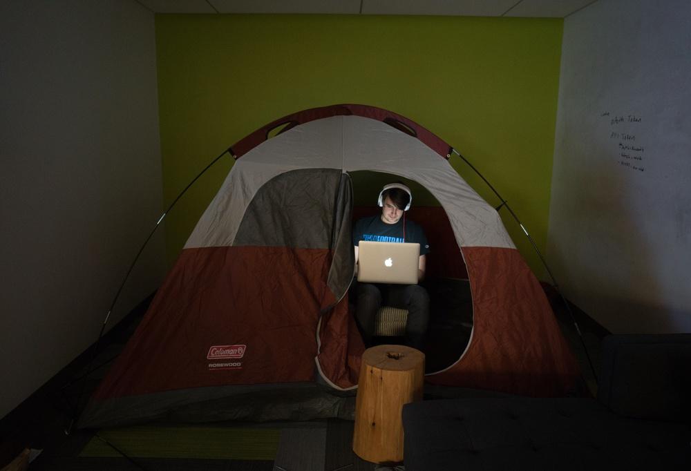 Bobby Tables, Software Developer, hacks away inside a tent.