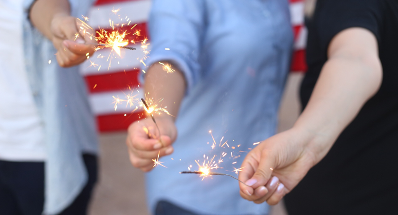A group of kids playing with sparklers on the Fourth of July.