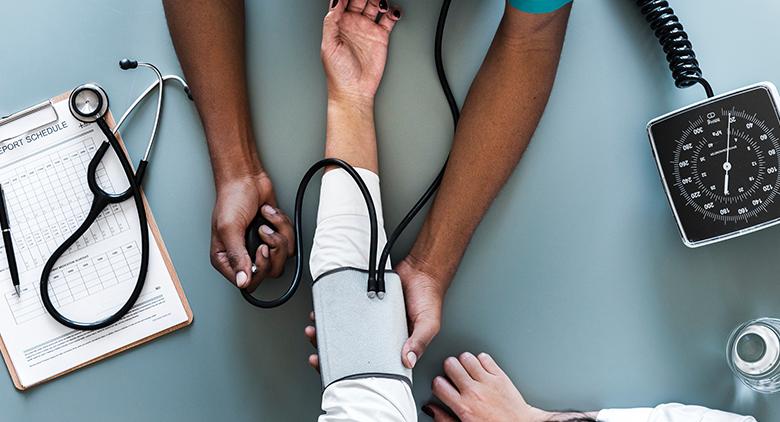 A black nurse taking a white patient's blood pressure.