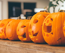 A group of Halloween jack-o-lanterns placed in a line.