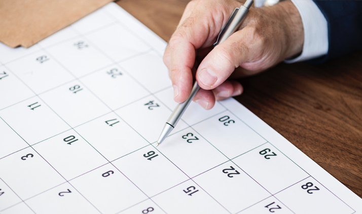 A white male's hand holding a pen and pointing to a company holiday date on the calendar.