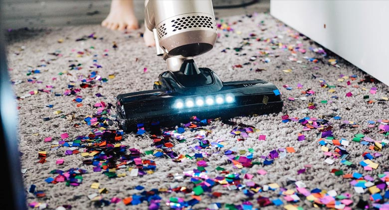A gig economy worker vacuuming confetti from a floor.