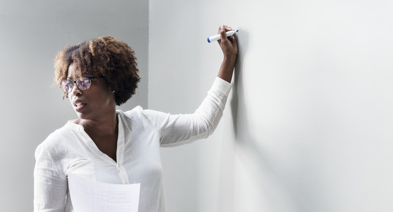 A black female HR manager writing development strategies on a wall to develop her employees.
